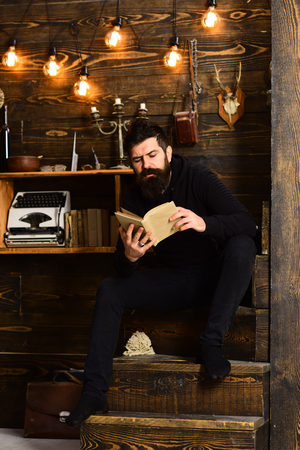 Best weekend. Man with beard holds old book and read. Guy in cozy warm atmosphere relaxing while reading Man bearded enjoy evening with favourite literature, wooden background