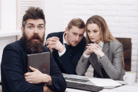 Startup concept. Business negotiations, discuss conditions of deal. Business partners or businessman at meeting, office background. Man with beard and folder proposes extraordinary startup idea