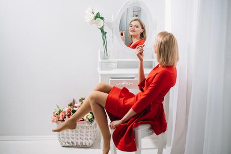 Moda y estilo empresarial. Maquillaje perfecto. Mujer sexy se puso lápiz labial en el espejo. Look de niña o mujer de negocios con maquillaje. Salón de belleza o tocador. Cosmética y cuidado de la piel de moda. Foto de archivo