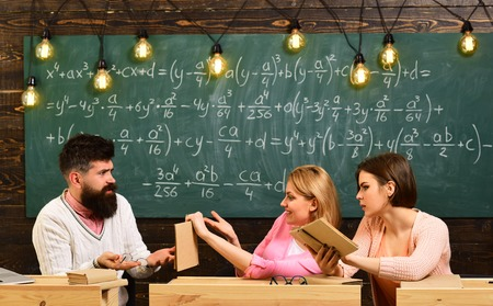 Girls students and bearded teacher, lecturer, professor. College and education concept. Students, young scientists studying, holds book , while professor teaches, explains, chalkboard background