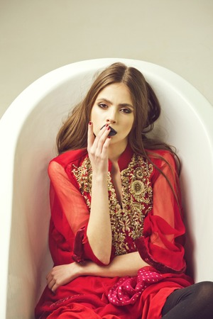 Female fashion, beauty and advertisement concept. white bath tub and beautiful young woman with black lips