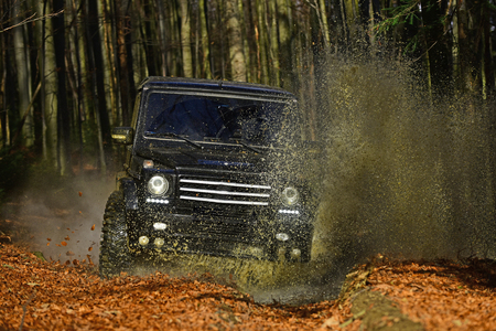 Extreme, challenge and 4x4 vehicle concept. SUV or offroad car on path covered with leaves crossing puddle with dirty water splash. Car racing in autumn forest Offroad race on fall nature background