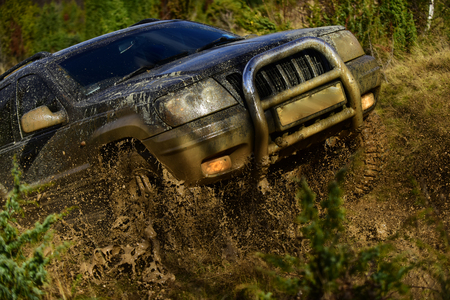 Car with strong chassis and the wheel axle crossing puddle with dirt splash. Automobile racing, car wash and off road vehicle concept SUV takes part in racing on fall nature background Stock fotó