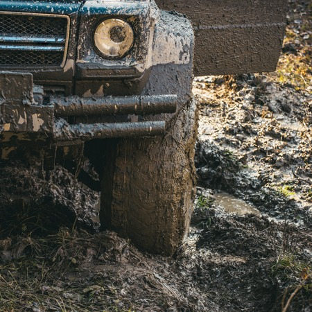 Dirty offroad tire covered with mud. Wheel in deep rut Stock Photo - 103717412