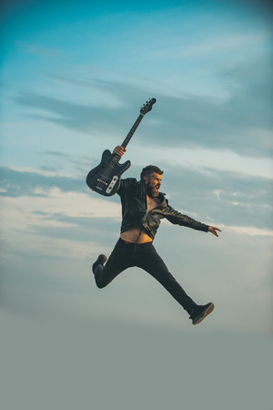Freedom in his veins. Freedom, bearded man jump with guitar on blue sky