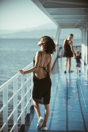 beautiful woman on ship with man and son. beautiful woman with little boy and man on yacht.
