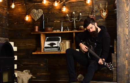 Spending great time at home. Man with beard holds black electric guitar. Guy in cozy warm atmosphere play music. Man bearded musician enjoy evening with bass guitar, wooden background