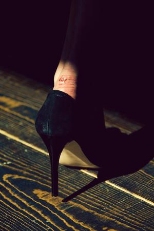 skincare. rub on leg in black fashionable shoe of glamour woman
