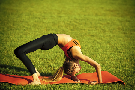Flexibility and stretching. Sportswoman training on green grass, sport woman Stock Photo