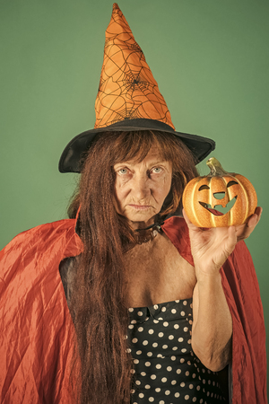 Halloween senior lady with long red hair in witch hat