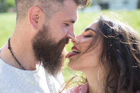 Playful couple feel flirty. Sensual woman stick out tongue to man. Kiss me right now. Bearded man and woman enjoy intimacy. Couple in love on sunny outdoor