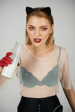 Portrait of beautiful model in cat costume drinking milk from bottle. Stock Photo - 103637362