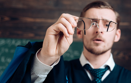 Let me see. Teacher formal wear and glasses looks concentrated, chalkboard background. Chalkboard full of math formulas. Man in end of lesson checking mistakes. Teacher finished explanation