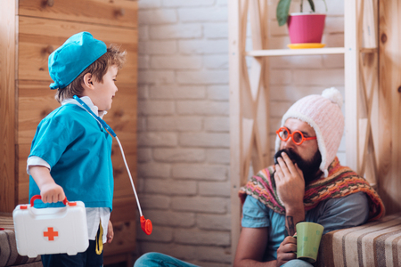 Discussing treatment. Medicine and health. Little child play doctor with man. Son with first aid box take care of father at home. Boy in doctor uniform treat patient. Game and development Foto de archivo