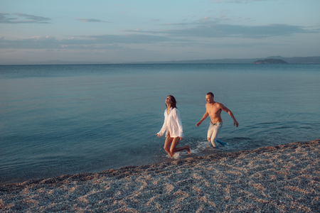 Couple in love run on sea or ocean beach in water splash. Freedom concept. Woman wears male shirt and running in sea waves. Man catches up with woman, play game, have fun