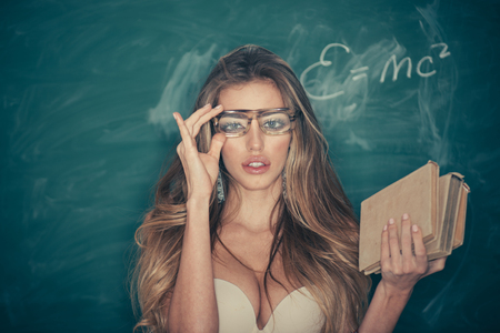 Confident and sexy teacher. Sensual woman adjust glasses on makeup face. School and education for adult. Woman with long blond hair in bra pose at chalkboard. Sexi bookworm. Back to school Stock Photo