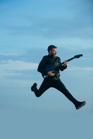 Music is so much fun. Bearded man jump with guitar on blue sky. Hipster guitarist with beard on excited face play in clouds. Like rock star. Feeling free and happy. I love my guitar