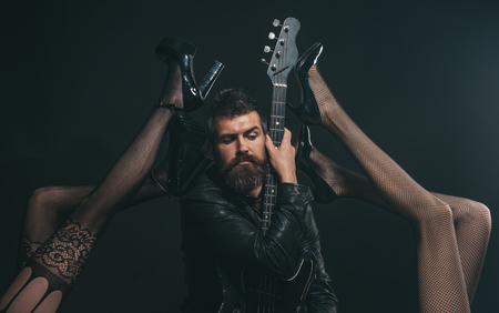 Music is his passion. Bearded man with guitar tempted by sexy legs in fetish lingerie. Feeling flirty. Like rock star. Attractive and sensual Фото со стока