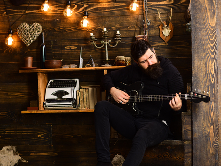 Man with beard holds black electric guitar. Guy in cozy warm atmosphere play music. Man bearded musician enjoy evening with bass guitar, wooden background. Spending great time at home
