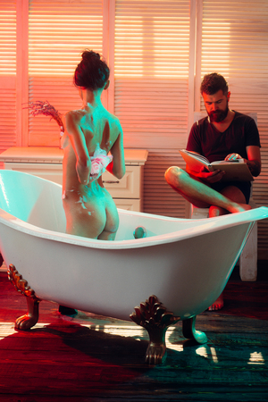 Bearded man read book while naked girl wash with wisp. Sex games desire and orgasm. Couple in love with sexy body. Massage and family spa concept. Love relations of couple in bath with foam.