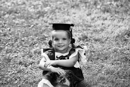child is a genius. The child is a child prodigy. Cute little girl with long hair in black graduation cap Stock Photo