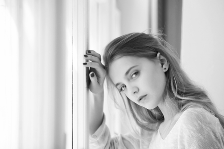 Caucasian female fashion model posing. Pretty girl with blue eyes standing at window