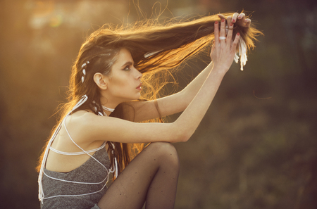 Beauty fashion portrait. girl with long fashionable indie hairstyle on natural background