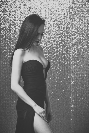 Beauty fashion portrait. Woman in black evening dress with sexy cleavage