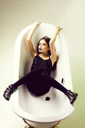 Fashionable woman posing. sexy woman in dress with black lipstick in bath