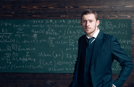 Talented mathematician. Teacher smart student intrested math physics exact sciences. Man formal wear classic suit looks smart, chalkboard with equations background. Genius solved mathematics problem
