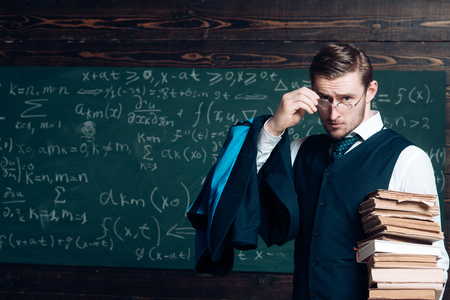 Teacher formal wear and glasses looks smart, chalkboard background. Man in end of lesson takes off eyeglasses. Teacher finished explanation. Did you get it Chalkboard full of math formulas Stok Fotoğraf