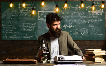 Scientist make research with microscope. Businessman wear glasses at desk. Man with beard and mustache in university. Bearded man with book and retro typewriter. Research or knowledge and innovation Banque d'images - 103833031