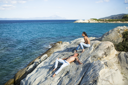 Sensual nude attractive couple on pensive faces. Sexy topless couple sits, lies on stone or reef in sea. Happy family spend time together, suntanning, sea surface background. Honeymoon concept Stock Photo - 103833054