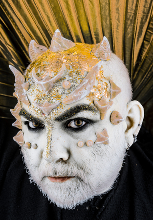 Head with thorns or warts, face covered with glitters, close up. Alien, demon, sorcerer makeup. Senior man with beard, with monster makeup. Demon with golden collar, black background. Fantasy concept.