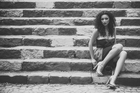Beauty Fashion model girl. Fashion look. Young woman on stairs