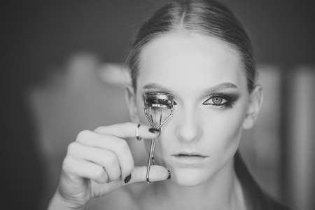 Beauty Fashion model girl. Fashion look. Woman curl lashes with beauty tool, look. Woman use eyelash curler for eye makeup. Model with curly long eyelashes, beauty Stock Photo