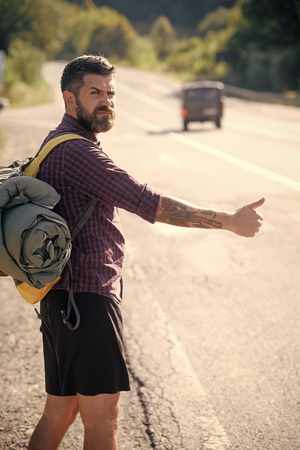 Hitchhiking. Hipster hiker show thumbs up hand gesture on sunny day. Man with backpack hitchhiking on road. Summer vacation concept. Tourist traveler travel auto stop. Adventure, discovery, wanderlust.