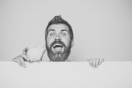 Sale and black friday shopping. Crisis and loan. Bankruptcy and handout. Man with beard on happy face take credit. Guy hold moneybox or piggy bank for savings. Stockfoto