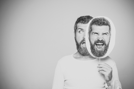 Beauty Fashion model man. Fashion look. Guy or bearded man on grey background. Feeling and emotions. Hipster with surprised and angry face hold portrait nameplate. Man with long beard and mustache. Stockfoto
