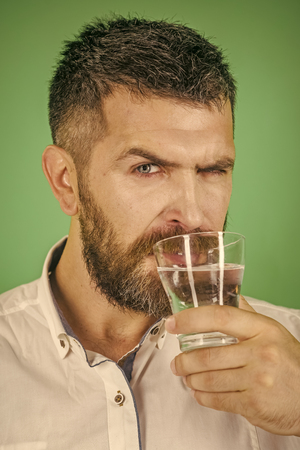 man with beard on serious face drink water from glass on green background, healthcare and life source, hangover and thirst, refreshing Imagens