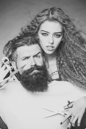 Beauty Fashion model couple. Fashion look. Portrait closeup couple of long-haired young beautiful woman holding scissors trying to cut long beard of grey-haired man with moustache and eyebrow raised o