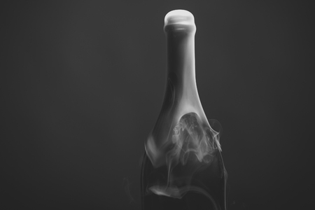 Open the bottle with champagne. Closeup view of one new open full champagme wive sweet or dry drink green glass bottle with beautiful white smoke for celebration christmas or new year in studio on grey background, horizontal picture