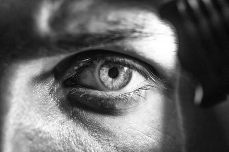 purposeful look. male eye with flashlight Banco de Imagens