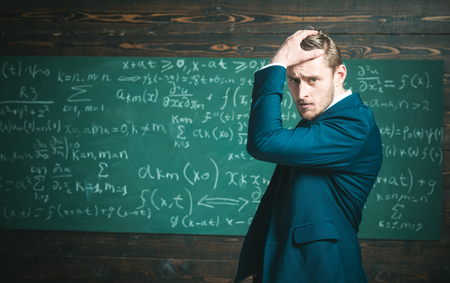Unproven theorem. Man formal wear classic suit looks smart, chalkboard background. Genius suffers unresolved mathematics problem. Man formal wear work on theorem, chalkboard with equations background Banco de Imagens