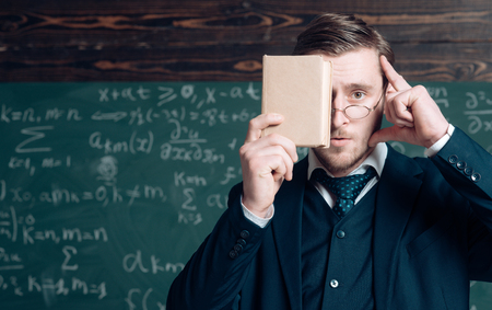 Keep in mind. Teacher formal wear and glasses looks smart, chalkboard background. Man unshaven holds book in front of face. Teacher insists on need to k eep in mind information. Education concept