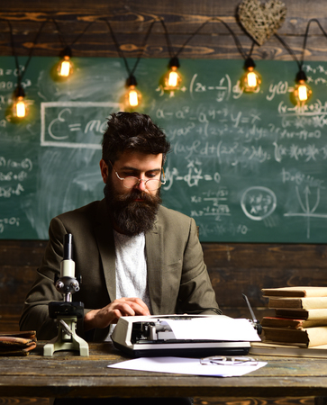 Bearded man type on vintage typewriter. Man with beard typewrite research paper. Businessman in suit work at desk. Scientist in glasses with microscope and books. Future and archaism