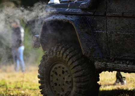 Part of vehicle covered with mud and man near it. SUV on nature background, close up. Side of car covered with dirt and cloud of smoke Off road racing, force and extreme entertainment concept