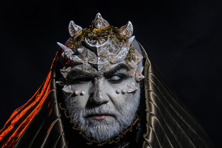 Senior man with white beard dressed like monster. Man with thorns or warts, face covered with glitters. Fantasy concept. Demon with golden hood on black background. Alien, demon, sorcerer makeup Stock Photo
