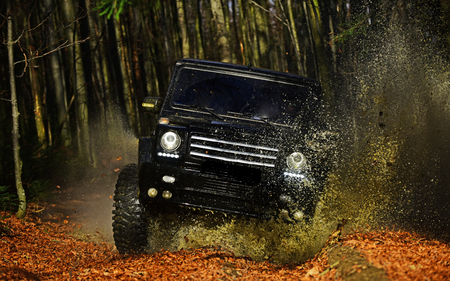 SUV or offroad car on path covered with leaves crossing puddle with dirty water splash. Offroad race on fall nature background Car racing in autumn forest. Extreme, challenge and 4x4 vehicle concept