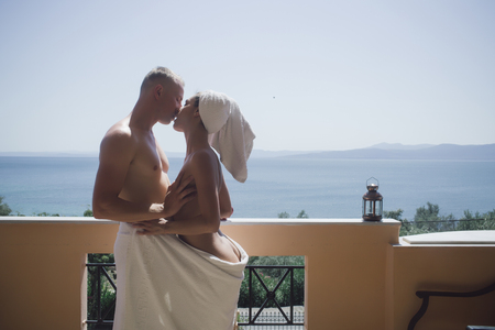 couple in love wrapped in a towel, hugging and kissing on the balcony Zdjęcie Seryjne - 105647896